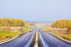 Straight road among autumn fields in the sunny day Stock Image