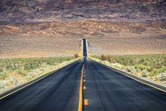 Straight road through barren desert of Death Valley National Park Stock Image