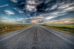 Straight road through countryside fields. With dramatic high contrast sky above Royalty Free Stock Photo