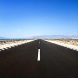 Straight road in desert. Cabo de Gata, Andalusia. Straight road in a desert seascape in a sunny day. Cabo de Gata, Andalusia, Spain Stock Image