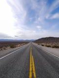 Straight road in desert landscape Stock Images