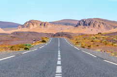 Straight road in desert. Leading to the mountains Royalty Free Stock Image