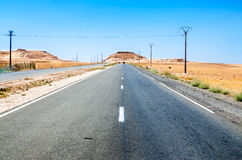 Straight road in desert leading to small mountains Royalty Free Stock Photos
