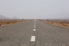Straight road through the desert in Morocco, Africa Royalty Free Stock Images