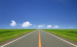 Straight road. Straight and empty road running through fields Royalty Free Stock Photography