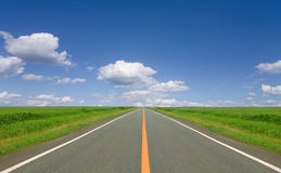 Straight road. Straight and empty road running through fields Royalty Free Stock Image