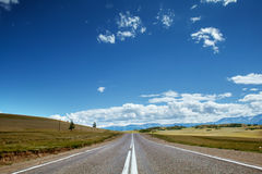 Straight road goes to horizon. On background of sky and mountains. Altay mountains, Siberia, Russia Stock Photography
