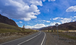 Straight road goes to horizon on mountains backdrop Stock Photos