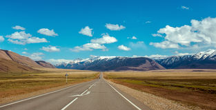 Straight road goes to horizon on mountains backdrop Stock Photography