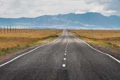Straight road goes to horizon and mountains Stock Photo
