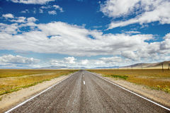 Straight road goes to horizon and mountains Royalty Free Stock Photography