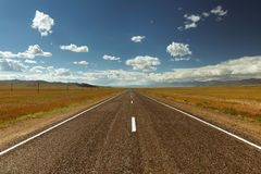 Straight road goes to horizon and mountains Royalty Free Stock Photo