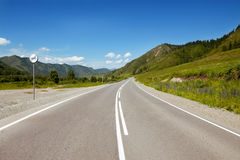 Straight road goes to horizon and mountains Stock Images