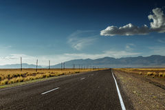 Straight road goes to horizon and moutains Stock Images