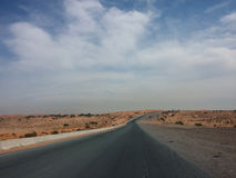 Straight Road. Road Going straight Ahead with clouds Stock Image