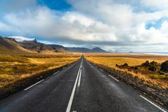 Straight Road Through Lave Fields under Cloudy Sky with Patches of Blue in Autumn. Straight Road through Lava Fields and Volcanic Mountains in Iceland on a Sunny royalty free stock photo