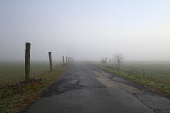 Straight road into light. Country road with fence posts heading toward sunrise in thick fog Royalty Free Stock Photography
