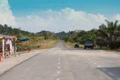 Road going into distance in Asia. A straight road in Malaysia going into the distance, with some stalls in the side on a sunny day stock image