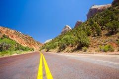 Straight road through mountainous area Stock Images