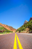 Straight road through mountainous area Stock Images
