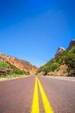 Straight road through mountainous area. Utah, USA Stock Images
