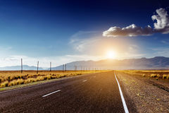 Straight road in mountains concept. Straight road goes to horizon and mountains in sunlight concept Royalty Free Stock Photos