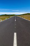 A straight road over the area with a blue sky with any clouds in the distance Royalty Free Stock Photos