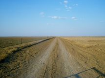 Straight road. A straight road running parallel with the fence in the desert Stock Photo
