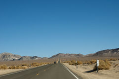 Straight road section through the desert and clear blue sky royalty free stock photography