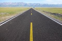 Straight road with snow mountains Stock Photography