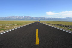 Straight road with snow mountains Royalty Free Stock Images