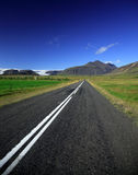 Straight road to the glacier. Against a bright blue sky Iceland Stock Photos