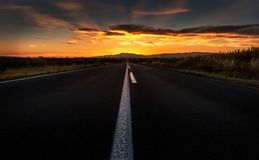 Straight road to sunset. Straight highway road to a dramatic fiery sunset Stock Photos