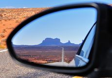 Road to Monument Valley reflected in car mirror. Straight road towards Monument Valley as refected in the rear-view mirror of a car, USA Stock Photo