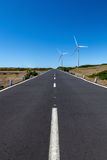 A straight road with two wind turbines over the area with a blue sky Stock Photography