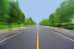 Straight road under blue sky. Straight road with trees,Motion blur Royalty Free Stock Photo