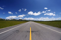 Straight road under blue sky Stock Photo