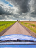 Straight Road under Brooding Sky. Blue Car on a Long Straight Road with Dark Cloudy Sky as a Concept for an Uncertain Economic Future Stock Images