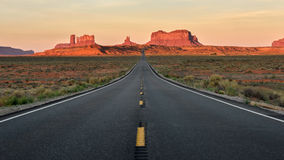 Straight Road vanishing into Monument Valley. Morning light on the rocks of Monument valley Stock Photos