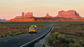 Straight Road vanishing into Monument Valley. School bus and morning light on the rocks of Monument valley Royalty Free Stock Image