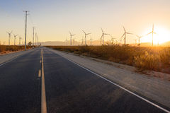 Straight road through the windfarm at sunset Stock Image