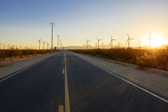 Straight road through the windfarm at sunset Royalty Free Stock Photos