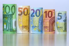 Straight row of accurately rolled hundred, fifty, twenty, ten and five new paper euro banknotes isolated on white background. Symb Royalty Free Stock Photo