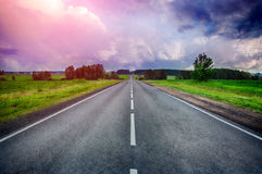 Straight rural road at the sunset. With a dramatic sky Royalty Free Stock Photography