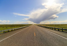 Straight to the Horizon. Straight road with two cars in the back running through grassland Royalty Free Stock Image