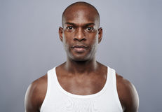 Straight on view of handsome man in undershirt. Straight on view of young single handsome African man with calm expression in white sleeveless undershirt Stock Images