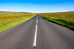 Straight way to target. Straight asphalt road with a white line to the horizon between the fields and grass. County Antrim, Northern Ireland, UK Stock Photo