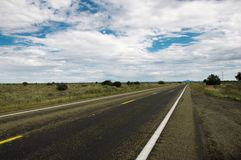 Straight wet road. Leading through Arizonas beautiful prairie Stock Image