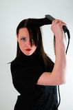 Straighten My hair. Female model straightening her hair against a white back drop Royalty Free Stock Photo