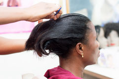 Straightening hair of the client. Royalty Free Stock Photos